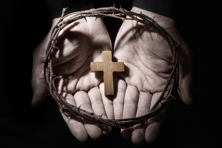 predicador: closeup of the hands of a young caucasian man with a small wooden cross and a crown of thorns
