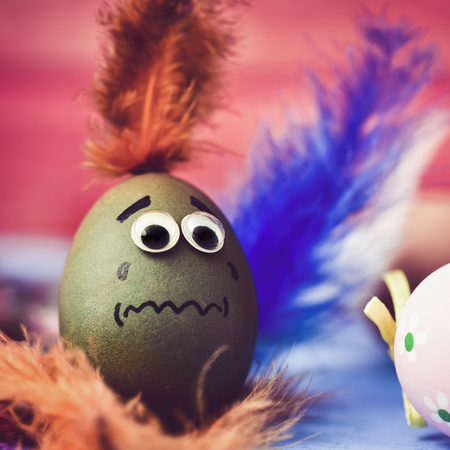 closeup of a green easter egg ornamented with three-dimensional eyes and a drawn mouth, with a scared face, surrounded by feathers of different colors Stock Photo