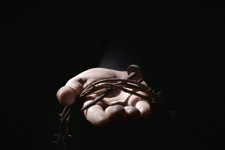 spiritualism: closeup of the hand of a young caucasian man with a nail of Jesus Christ and a crown of thorns Stock Photo