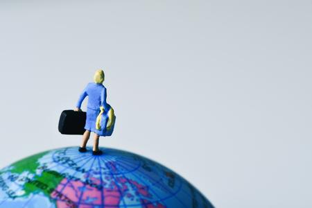 miniatuurreiziger vrouw van achteren gezien met enkele koffers, op de top van de aardbol Stockfoto