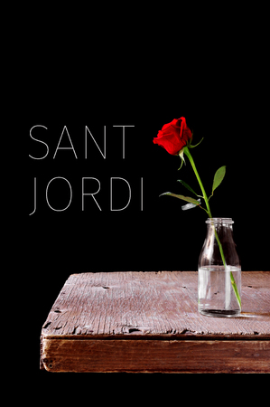 a red rose in a vase placed on a wooden table, over a black background and the text Sant Jordi, the Catalan name for the Saint Georges Day, when it is tradition to give red roses in Catalonia, Spain