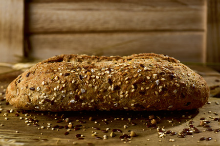 closeup of a wholemeal bread roll topped with different seeds, such as sesame and poppy seeds, on a rustic wooden table