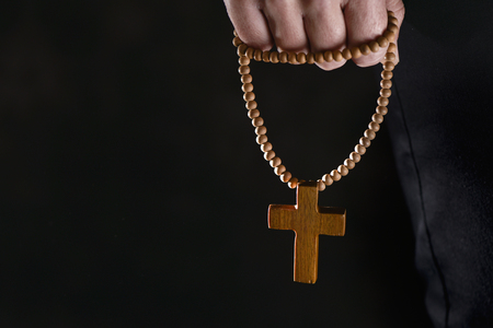 closeup of the hand of a young caucasian man praying with a rosary with a wooden cross in it, against a black background with a blank space