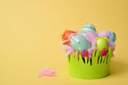 a pile of different decorated easter eggs in a basket decorated as grass and some pink feathers against a yellow background with a blank space on the left