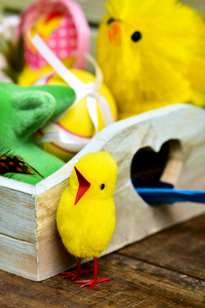 closeup of some some toy chicks and some different decorated easter eggs in a rustic wooden tray, on a wooden surface Stock Photo