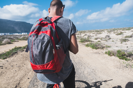 a young man with a backpack seen from on a bike, stopped to look to his smartphone or GPS, in a dirty road in La Graciosa, Canary Islands, Spain