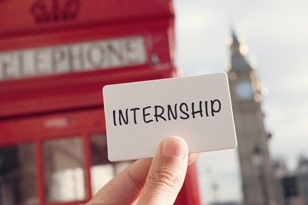 the hand of a young man showing a signboard with the word internship with a red telephone booth and the Big Ben in the background, in London, United Kingdom