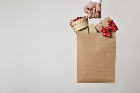 closeup of the hand of a young caucasian man carrying a paper shopping bag full of gift boxes ornamented with red ribbon against an off-white background, and a negative space on the left