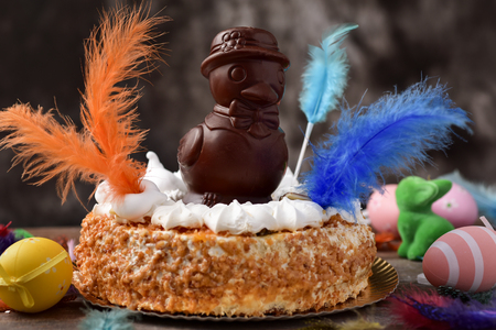 eastertime: a mona de pascua, a cake eaten in Spain on Easter Monday, topped with a chocolate chick, on a rustic wooden surface full of decorated eggs and feathers of different colors Stock Photo