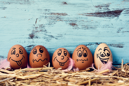 funny: some brown eggs with funny faces on a pile of straw, against a blue rustic wooden background with a blank space above them