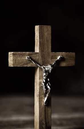 closeup of an old christian crucifix on a rustic wooden surface
