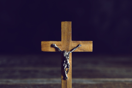 spiritualism: closeup of an old christian crucifix on a rustic wooden surface