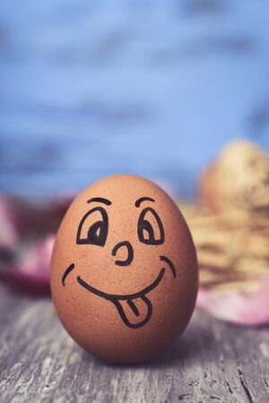 closeup of a brown egg with a funny face on a rustic wooden surface, against a blue rustic wooden background Stock Photo