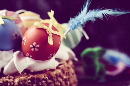 eastertime: a mona de pascua, a cake eaten in Spain on Easter Monday, topped with different decorated eggs and feathers of different colors, with a retro filter effect