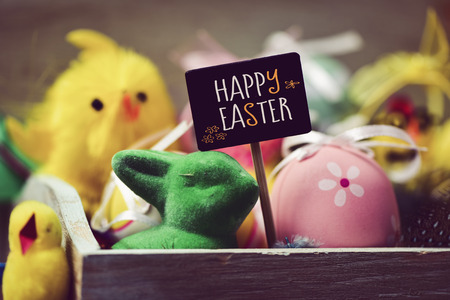 some yellow toy chicks, a green toy rabbit, some decorated eggs and a black signboard with the text happy easter
