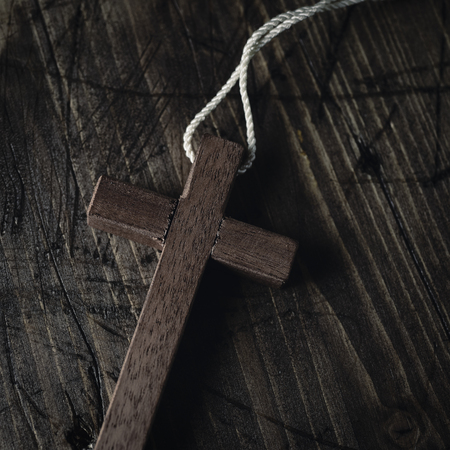 spiritualism: closeup of a small wooden cross with a cord tied to it, on a rustic wooden surface