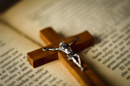 new testament: closeup of an old christian crucifix on an open bible, with a retro filter effect