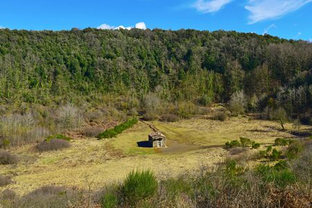 a view of the crater of the Santa Margarida Volcano in the Garrotxa Volcanic Zone Natural Park, in Olot, Spain, with the old small church dedicated to Saint Margaret in the center Banco de Imagens