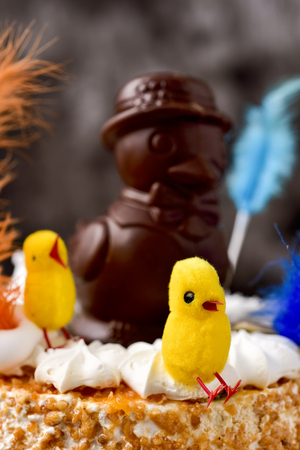 eastertime: a mona de pascua, a cake eaten in Spain on Easter Monday, topped with a chocolate chick and some yellow teddy chicks and decorated with feathers of different colors Stock Photo