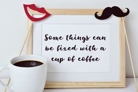 reflexive: a wooden-framed picture with the text some things can be fixed with a cup of coffee written in it, a red mouth and a mustache attached to sticks and a cup of coffee on a white surface