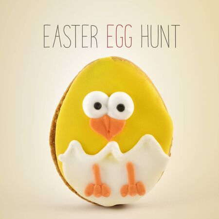 the text Easter egg hunt and a handmade cookie patterned as a funny chick emerging from an egg on a beige background