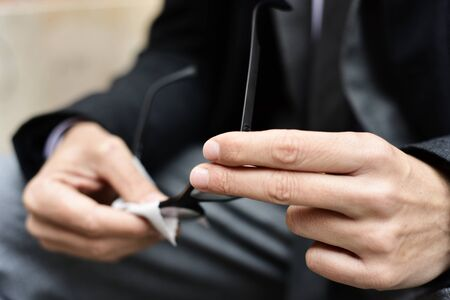 closeup of a young caucasian businessman in a gray suit and a dark coat cleaning the lenses of his eyeglasses with a microfiber cloth outdoors