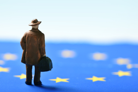 miniature traveler man seen from behind wearing a hat and carrying a suitcase, on an european union flag Stock Photo