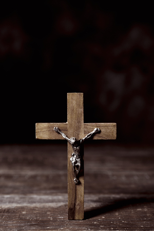 spiritualism: closeup of an old christian crucifix on a rustic wooden surface, with a blank space on top Stock Photo