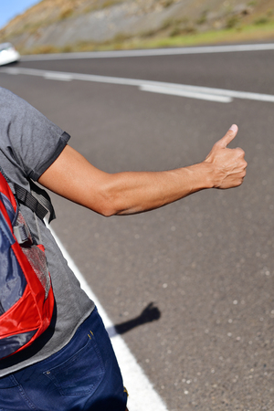 closeup of a young caucasian man seen from behind carrying a backpack hitchhiking in a minor road, with his thumb up Stock Photo