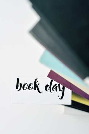 prose: a piece of paper with the text book day popping up from a book from a pile of books, placed on a white surface Stock Photo