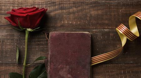 Una rosa roja, un libro antiguo y una bandera catalana, en una rústica mesa de madera, para Sant Jordi, el nombre catalán para el Día de San Jorge, cuando es tradición dar rosas rojas y libros en Cataluña, España Foto de archivo