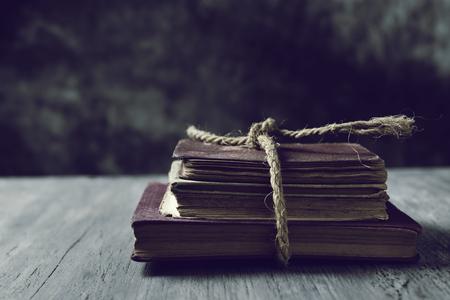 素朴な木製のテーブルの上で結ばれた本の山、ジュート文字列します。