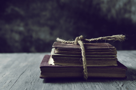 a pile of old books tied with a jute string on a rustic wooden table