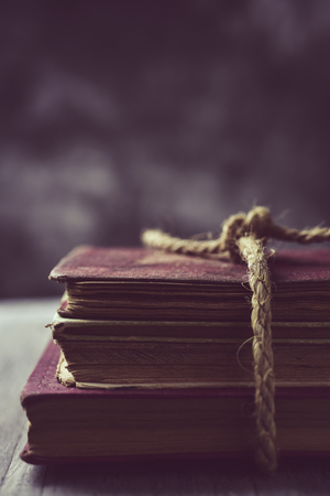 prose: a pile of old books tied with a jute string on a rustic wooden table
