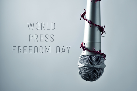 dictatorial: closeup of a microphone encircled by a red barbed wire and the text world press freedom day on a gradient gray background Stock Photo