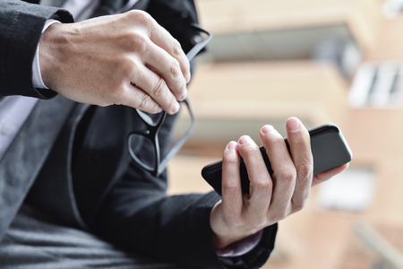 closeup of a young caucasian businessman in a gray suit outdoors using a smartphone with one hand and holding his eyeglasses in the other hand Stock Photo
