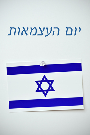israelite: the text day of israel written in hebrew and an israeli flag pinned with a push-pin to an off-white background
