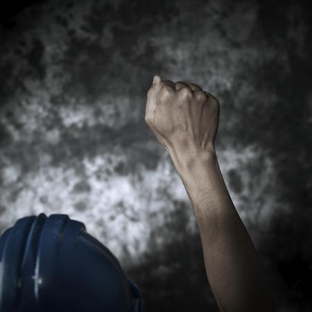 一个年轻的白人男子的特写从后面看到戴着蓝色的安全帽和他的拳头举起到空中,以灰色背景的梯度