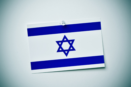 israelite: closeup of a flag of israel pinned with a push-pin to an off-white background with a vignette effect