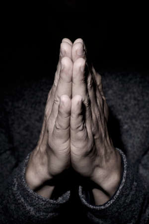 closeup of the hands of a young caucasian man praying with his hands put together