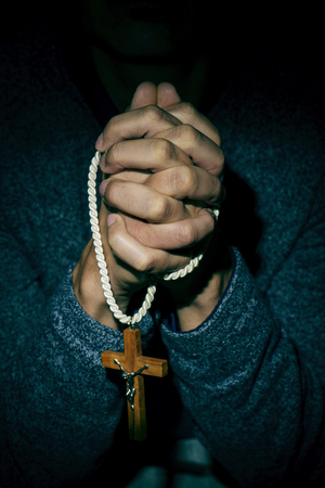 spiritualism: closeup of the hands of a young caucasian man praying with a wooden crucifix in them Stock Photo