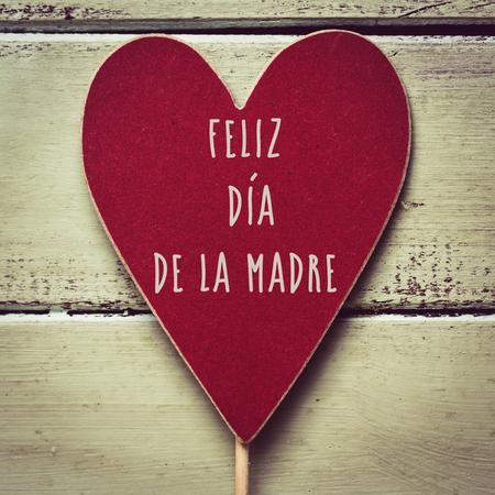 close-up van een rood hartvormig uithangbord met de tekst feliz dia de la madre, gelukkige moederdag geschreven in het Spaans, tegen een lichtgroene rustieke houten achtergrond