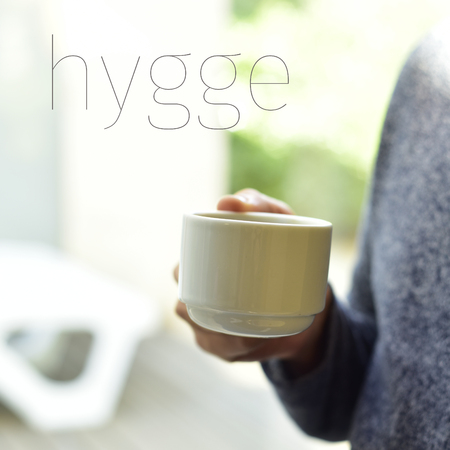 wholeness: closeup of a young man with a cup of coffee in his hand and the text hygge, a danish and norwegian word for comfort or enjoy, which can be a whole philosophy of life Stock Photo