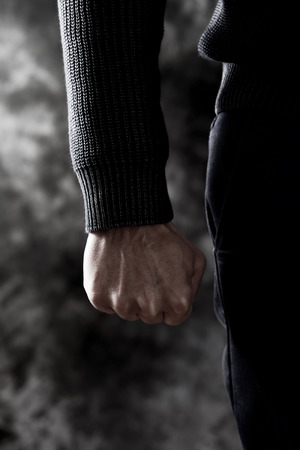 closeup of a young caucasian man in casual wear with a threatening gesture, clenching his fist Stock Photo
