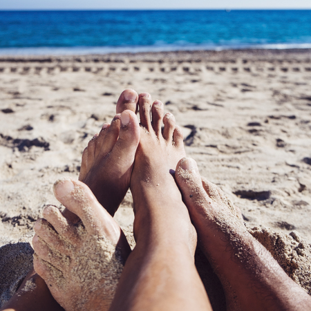 closeup of the feet of two young men playing footsie on the beach, with the sea in the background