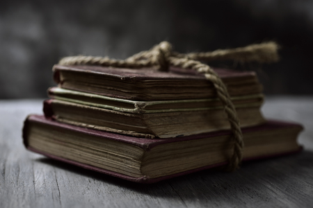 poems: a pile of old books tied with a jute string on a rustic wooden table