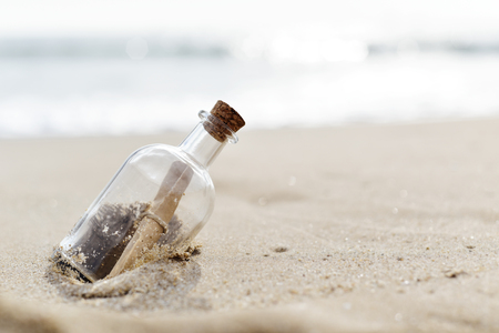 closeup of a glass bottle with a rolled message inside stranded in the sand of a lonely beach 免版税图像 - 77153840