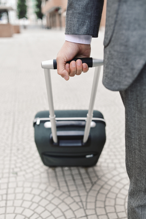 travelling salesman: closeup of a young caucasian businessman in an elegant gray suit pulling a trolley by its handle on the street