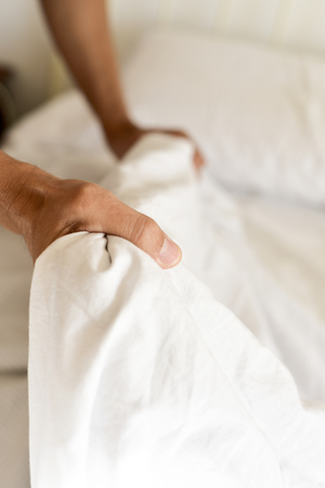 soltería: closeup of a young man extending the bedsheet or the duvet on the mattress as he is making the bed