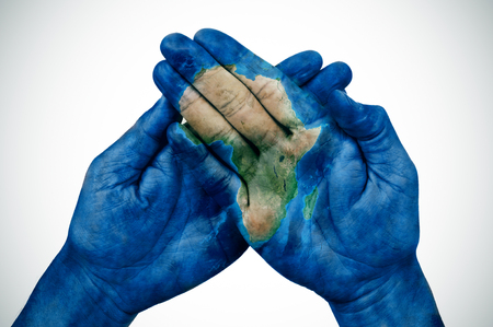 the hands of a young man put together patterned with a map of Africa (furnished by NASA)